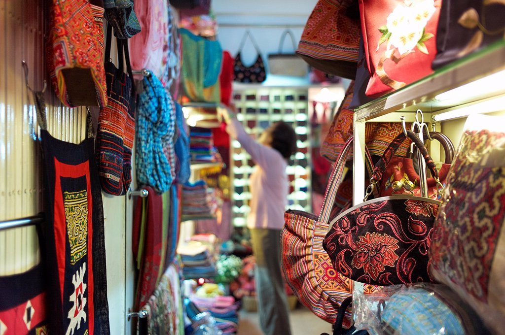 A shop owner shows off silk at the Nunal Boutique silk shop in Hanoi that sells colorful pieces of embroidered silk : Stock Photo