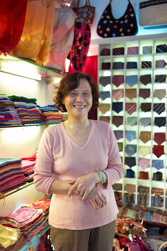 Stock Photo: 1566-1039775 A shop owner shows off silk at the Nunal Boutique silk shop in Hanoi that sells colorful pieces of embroidered silk
