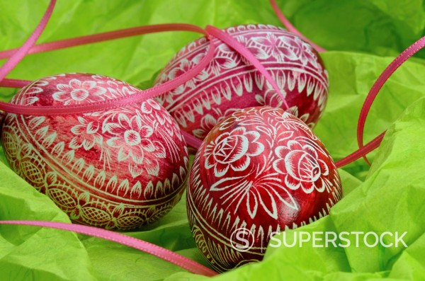 Stock Photo: 1566-1041017 Colored Easter Eggs with Ribbon on green Background