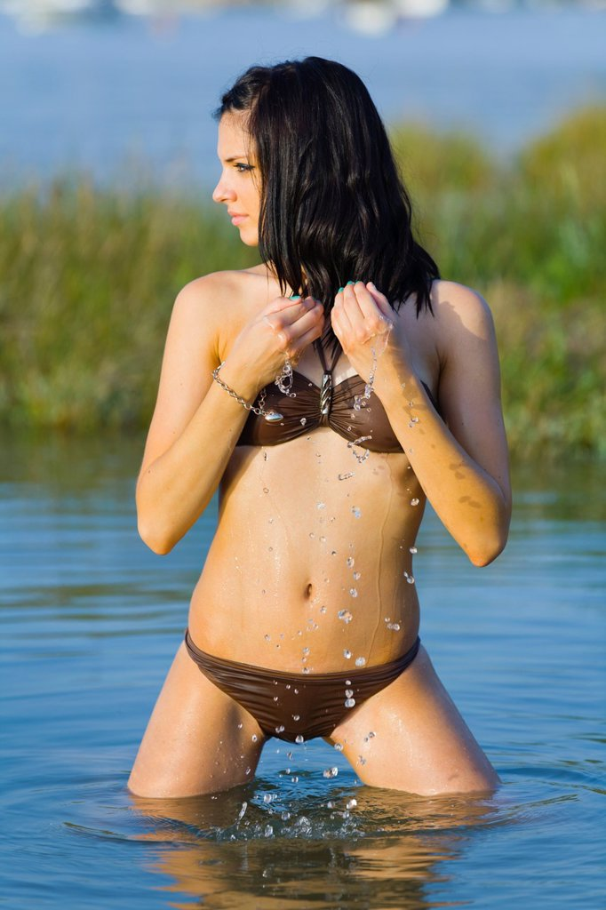Stock Photo: 1566-1044902 Young woman is cooling herself with water