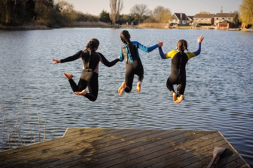 Three girls jumping into a lake while holding hands, England, UK : Stock Photo