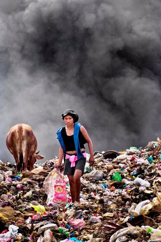 Stock Photo: 1566-1046401 A Nicaraguan girl works on the burning pile of garbage in the garbage dump La Chureca, Managua, Nicaragua, 4 November 2004  La Chureca is the biggest garbage dump in Central America  Hundreds of trash recollectors search in tons of smouldering garbage mai. A Nicaraguan girl works on the burning pile of garbage in the garbage dump La Chureca, Managua, Nicaragua, 4 November 2004  La Chureca is the biggest garbage dump in Central America  Hundreds of trash recollectors search in tons of smouldering