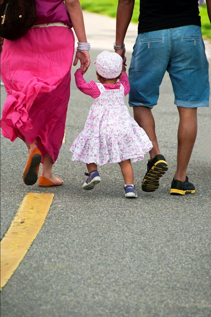 Stock Photo: 1566-1048393 young parents with their little daughter on a walk, symbol of caring family