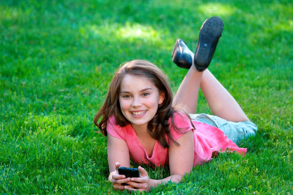 young girl lying on lawn listening to music : Stock Photo