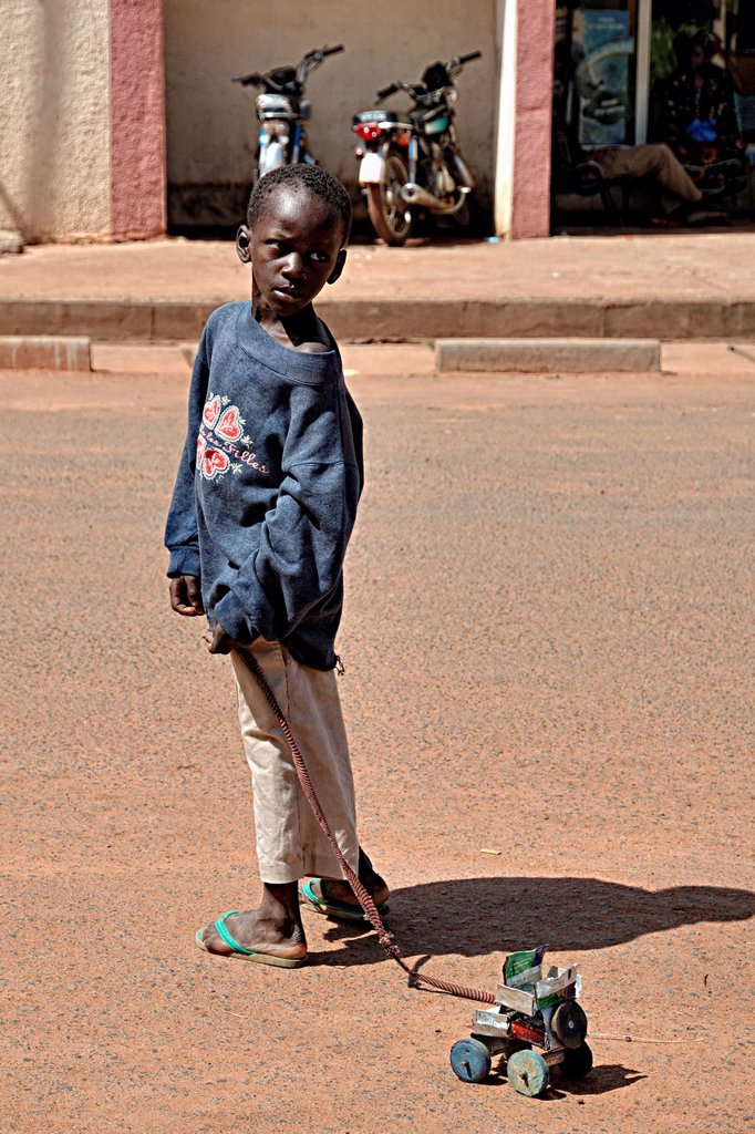 Stock Photo: 1566-1050140 A child drags his toy car made from recycled materials, Segou, Mali