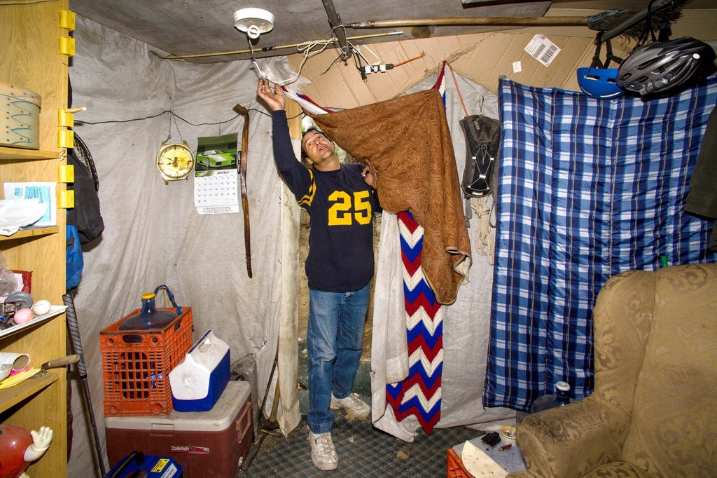 Stock Photo: 1566-1050207 A military veteran enters his makeshift shelter among homeless residents of a primitive outdoor encampment in the desert town of Victorville, CA  Note electric light
