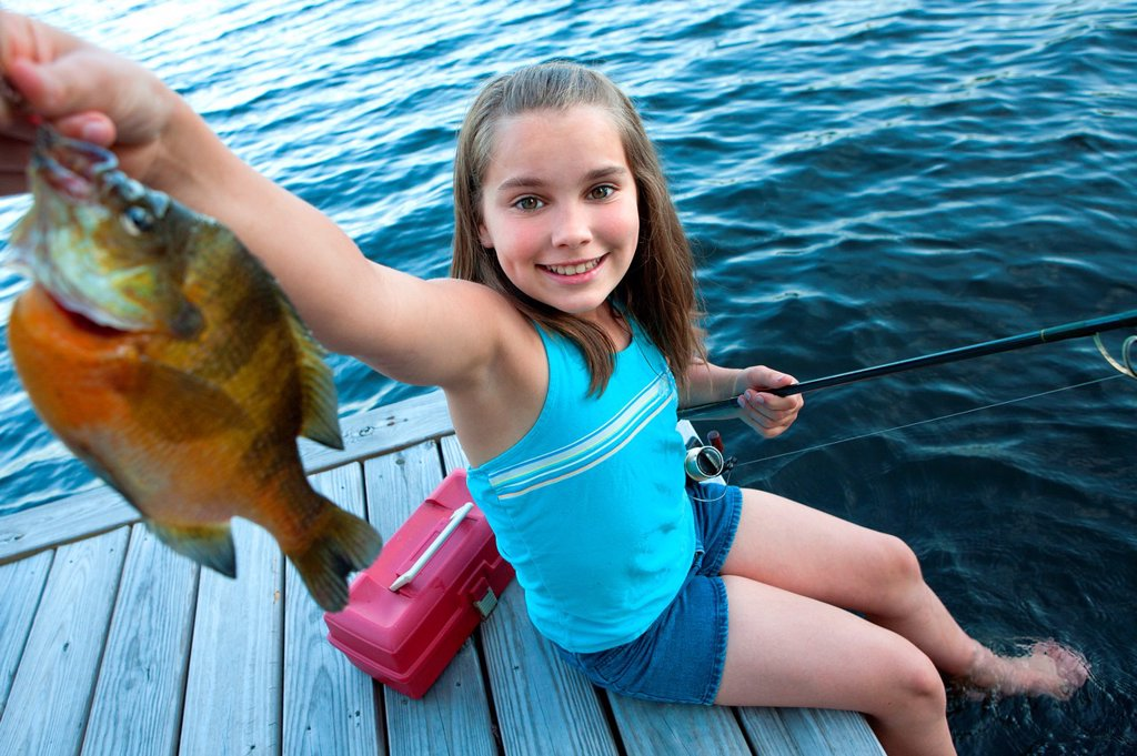 Stock Photo: 1566-1050283 Young girl proudly shows off fish she caught