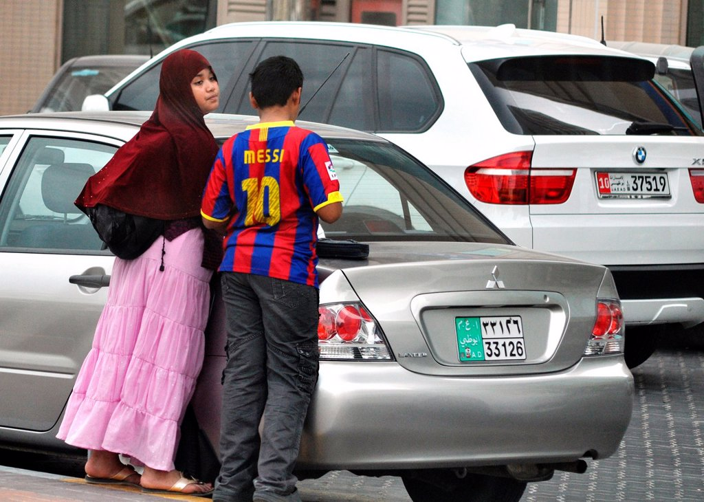 Stock Photo: 1566-1051102 Abu Dhabi, United Arab Emirates: veiled girl and boy with Messi's t-shirt