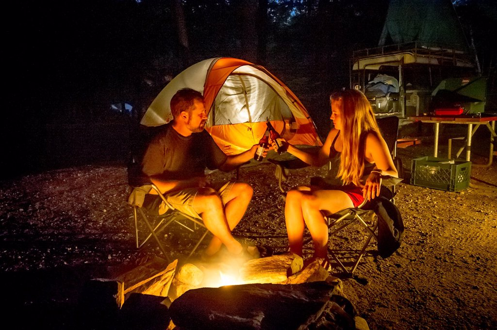 Stock Photo: 1566-1051535 Couple by campsite fire with tents Sebago Lake Maine USA