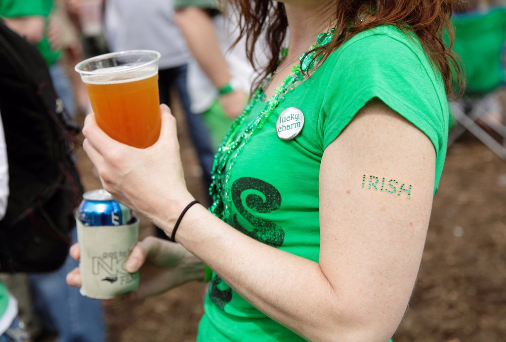 Stock Photo: 1566-1051673 A young woman with a beer in her hand and the word ´Irish´ affixed to her arm at a St  Patrick´s Day festival in Raleigh, North Carolina, USA