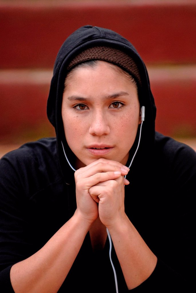 Young mixed raced woman in black sportswear, listening to music with headphones : Stock Photo