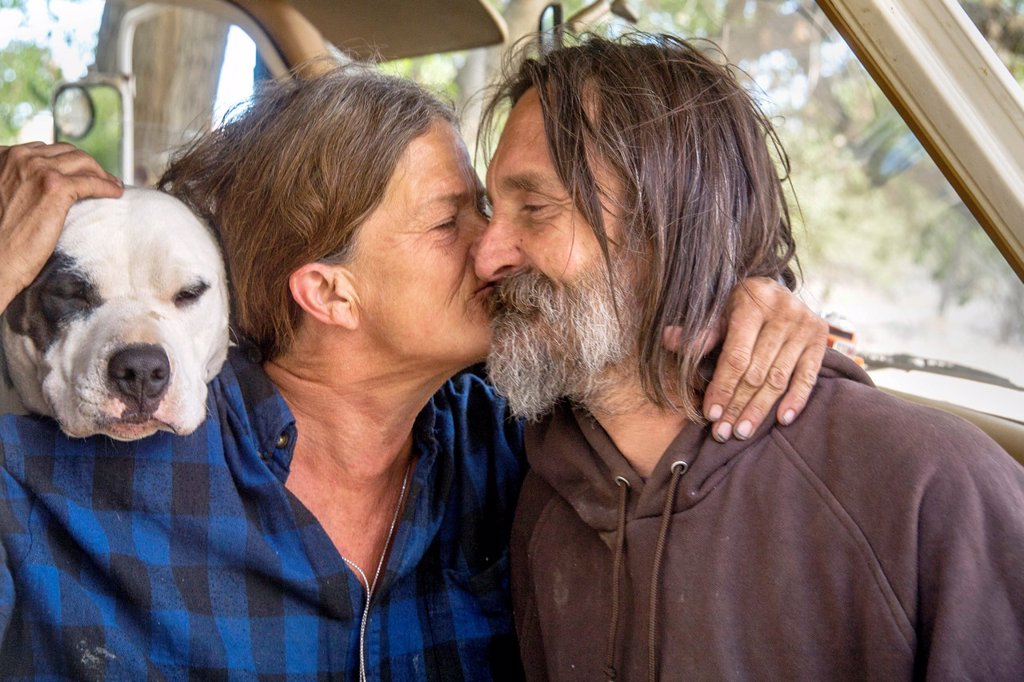 Stock Photo: 1566-1053059 An affectionate indigent couple and their dog live in a truck camper among homeless residents of a primitive outdoor encampment in the desert town of Victorville, CA