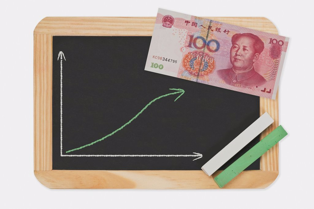 Stock Photo: 1566-1055526 Detail photo of a chalkboard. A chart with an increasing curve on this. On the chalkboard lies a Chinese 100 Yuan banknote with the portrait of Mao Zedong. Green and white chalk lies in a corner.