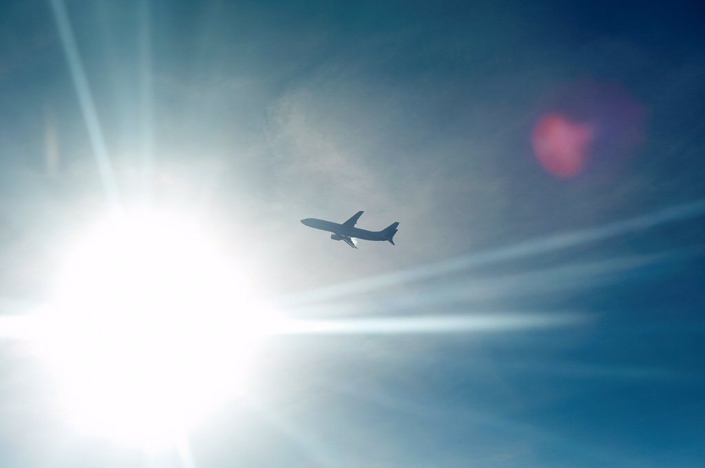 Stock Photo: 1566-1056329 An airplane backlit by the sun in midair