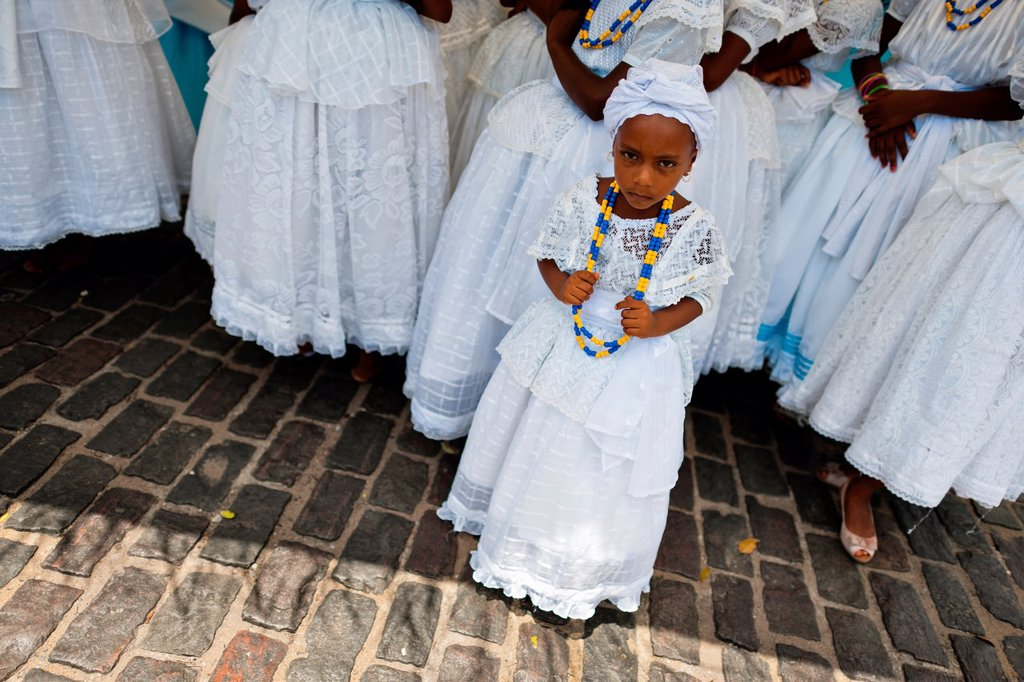 A young Baiana girl seen during the ritual ceremony in honor to Yemanjá, the Candomblé goddess of the sea, in Cachoeira, Bahia, Brazil, 5 February 2012  Yemanjá, originally from the ancient Yoruba mythology, is one of the most popular 'orixás', the deitie. A young Baiana girl seen during the ritual ceremony in honor to Yemanjá, the Candomblé goddess of the sea, in Cachoeira, Bahia, Brazil, 5 February 2012  Yemanjá, originally from the ancient Yoruba mythology, is one of the most popular 'orixás' : Stock Photo