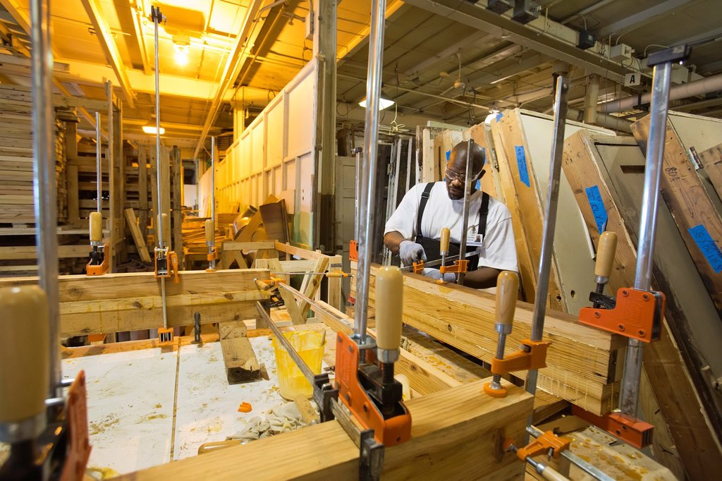Detroit, Michigan - A worker glues together reclaimed lumber to make butcher-block counter tops at a warehouse operated by the nonprofit WARM Training Center  The lumber was salvaged from homes being ´deconstructed ´ Deconstruction, an alternative to stan. Detroit, Michigan - A worker glues together reclaimed lumber to make butcher-block counter tops at a warehouse operated by the nonprofit WARM Training Center  The lumber was salvaged from homes being ´deconstructed ´ Deconstruction, an alterna : Stock Photo