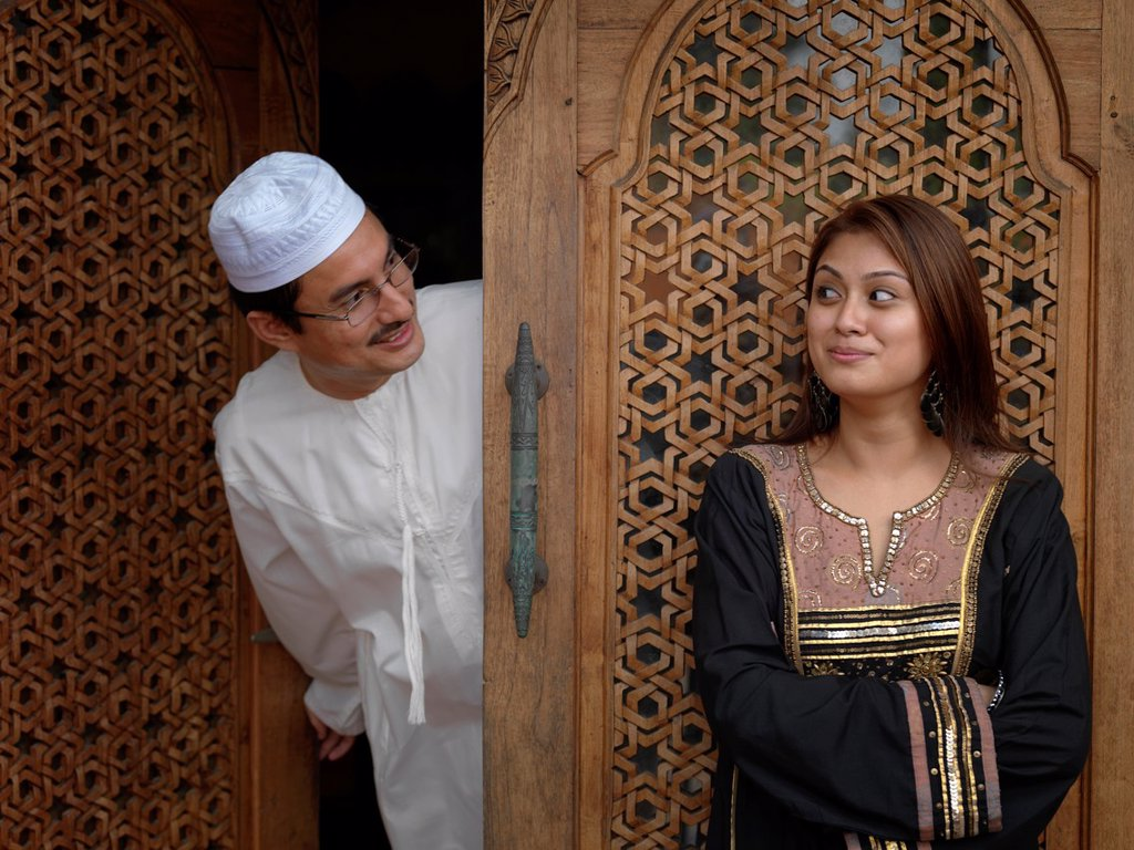 Stock Photo: 1566-1060449 Arab Muslim Malaysian father and daughter looking at each other in front of an intricately designed doorway
