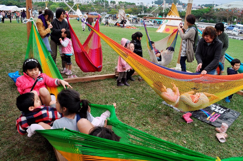 Nago Japan: children having fun on hammocks during the first commemoration of Fukushima's disaster : Stock Photo