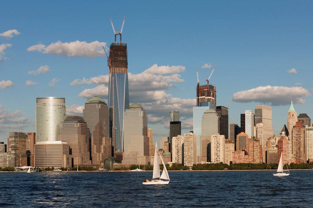 Stock Photo: 1566-1062050 Sailboats catch the breeze on the Hudson River in New York City late on a summer afternoon, with the buildings of the World Financial Center and the World Trade Center complex, including the Freedom Tower One World Trade Center, in the background