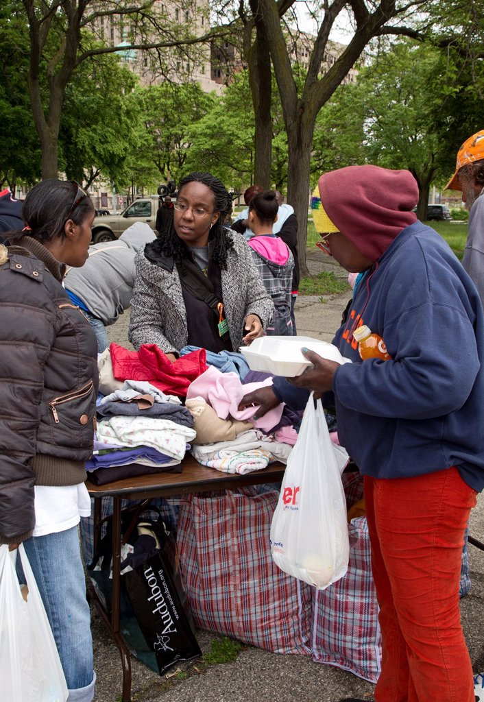 Stock Photo: 1566-1062712 Detroit, Michigan - Volunteers from United Christians in Christ church distribute clothing to homeless people in Cass Park
