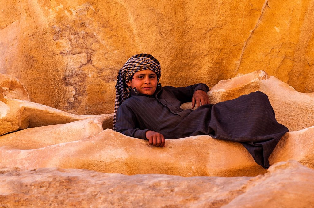 A Bedouin boy at the 100 foot tall Burdah Rock Bridge an arch, Wadi Rum, in the Arabian Desert, Jordan : Stock Photo