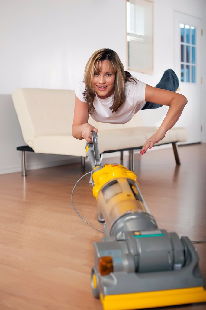 Woman hovering in air levitation style while vacuum cleaning the house : Stock Photo