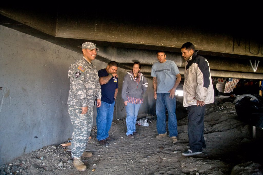 An official of the charitable outreach program Vet Hunters greets homeless military veterans living under a Southern California bridge  Supported by the U S  Army Reserve, the organization offers food and clothing to indigent veterans  Note uniformed sold. An official of the charitable outreach program Vet Hunters greets homeless military veterans living under a Southern California bridge  Supported by the U S  Army Reserve, the organization offers food and clothing to indigent veterans  Note un : Stock Photo