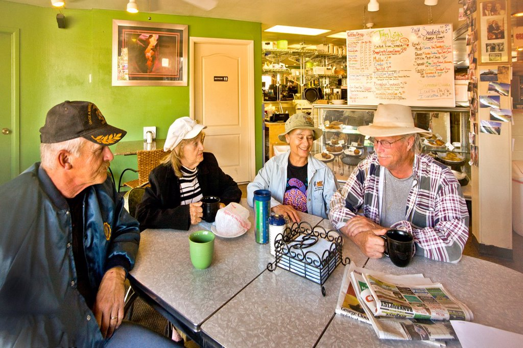 Local people their enjoy morning coffee and conversation at a Main Street restaurant in Kanab, Utah  Note sign in background : Stock Photo