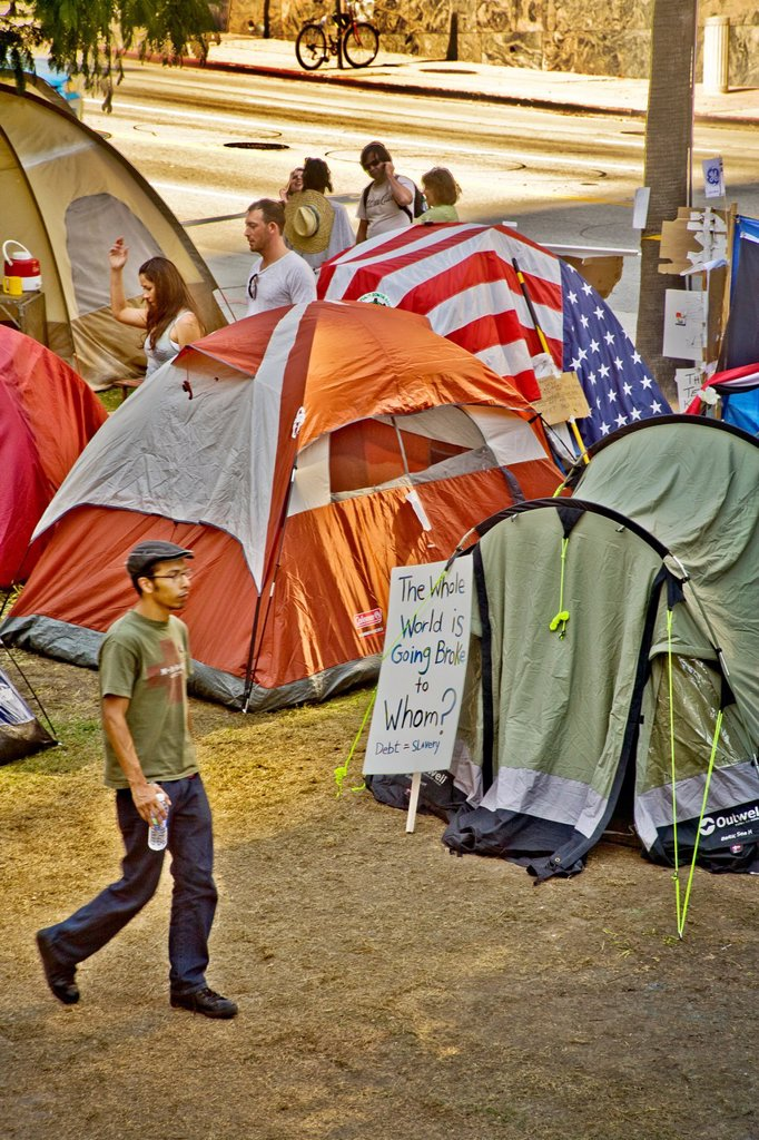 Stock Photo: 1566-1067841 Tents of the Occupy Wall Street protest at Los Angeles City Hall in October, 2011  Note sign saying ´The Whole World is Going Broke to Whom´Signs express the anti-establishment opinions of young Occupy Wall Street protesters occupying the grounds of Los A. Tents of the Occupy Wall Street protest at Los Angeles City Hall in October, 2011  Note sign saying ´The Whole World is Going Broke to Whom´Signs express the anti-establishment opinions of young Occupy Wall Street protesters occupying the grou