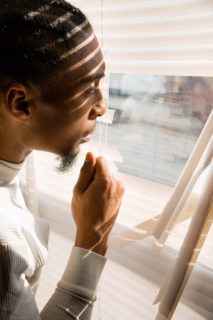 Stock Photo: 1566-1069852 Young black man looking out a window with broken blinds