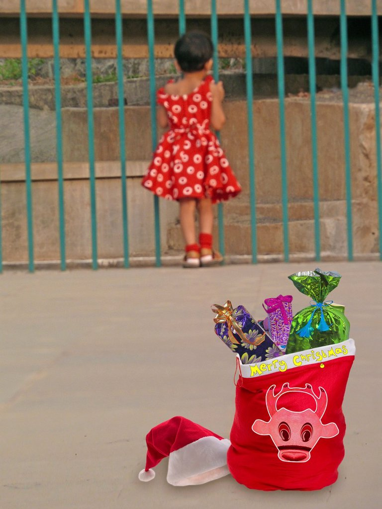 Surprised crismas gifts for a small girl in red dress : Stock Photo