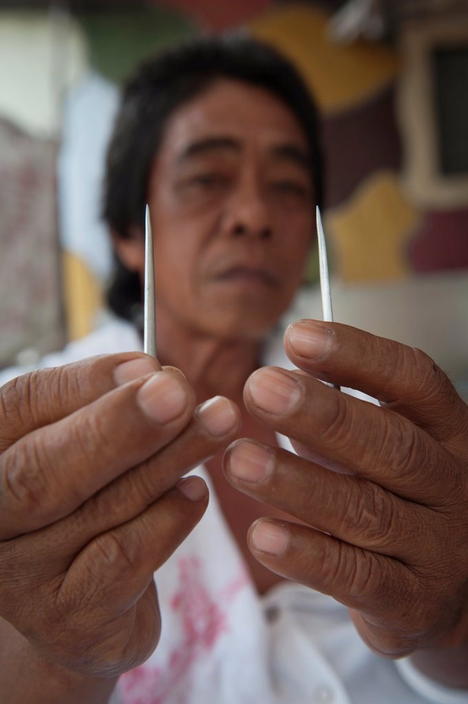 Stock Photo: 1566-1079169 Alex shows the nails before being crucified on Good Friday, San Fernando, Pampanga, Philippines