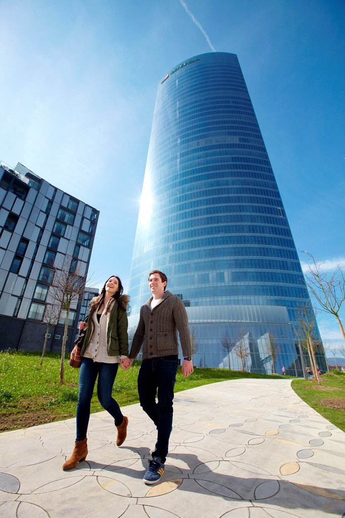 Stock Photo: 1566-1079363 Young couple walking, Iberdrola Tower, designed by Cesar Pelli, Abandoibarra, Bilbao, Bizkaia, Basque Country, Spain