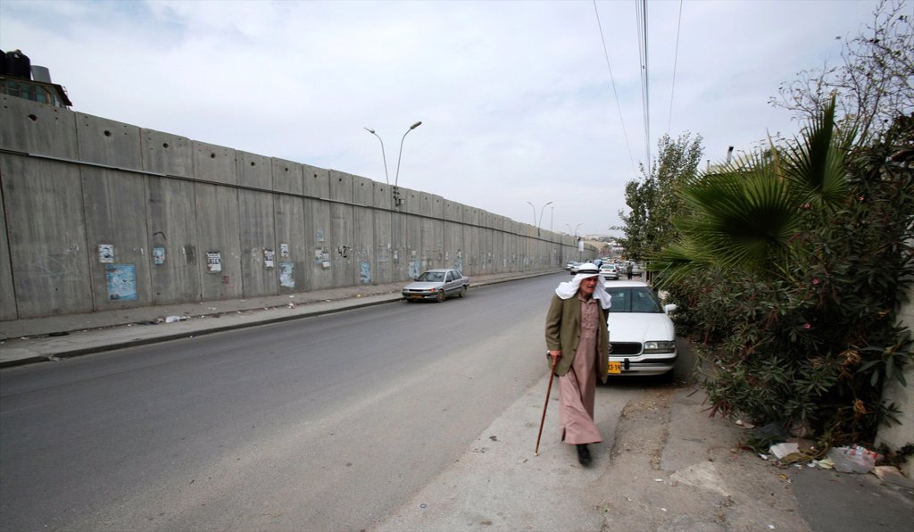 A man walks near the wall Israel is building around the west bank territories, blocking access for Palestinians who feel imprisoned by it : Stock Photo