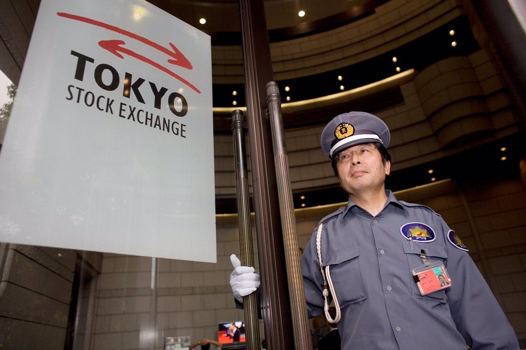 Stock Photo: 1566-1080278 a guard stands at the entrance of the tokyo stock exchange to keep angry customers out the building In october 2008, the stockmarkets in Tokyo lost their value in light of the financial crisis worldwide