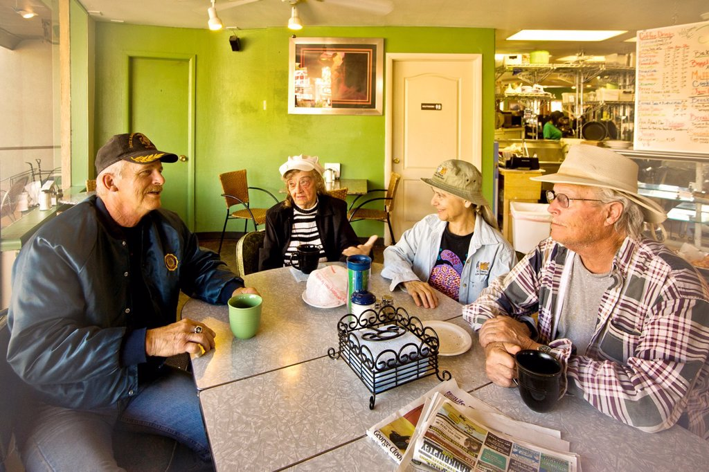 Stock Photo: 1566-1080853 Local people their enjoy morning coffee and conversation at a Main Street restaurant in Kanab, Utah  Note sign in background