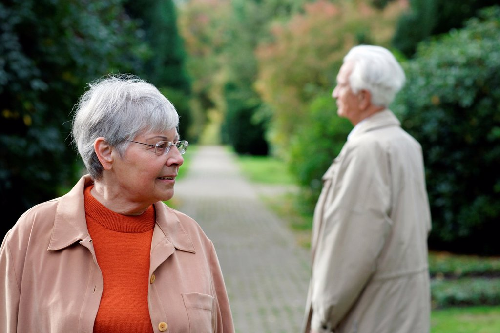 Stock Photo: 1566-1081593 Senior caucasian woman with glasses, looking to the side with senior man seen from backside, blurred green background, Hamburg, Germany, Europe