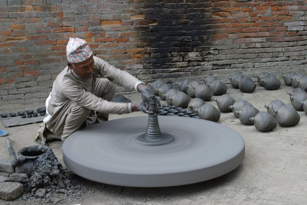 A man is making a clay pot for storing food and oils in Baktapur : Stock Photo