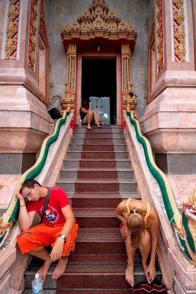 Stock Photo: 1566-1084559 Tired European tourists resting at entrance to Wat Chalong - Buddhist temple in Phuket, Thailand  Wat Chalong is the largest and the most visited of Phuket´s temples