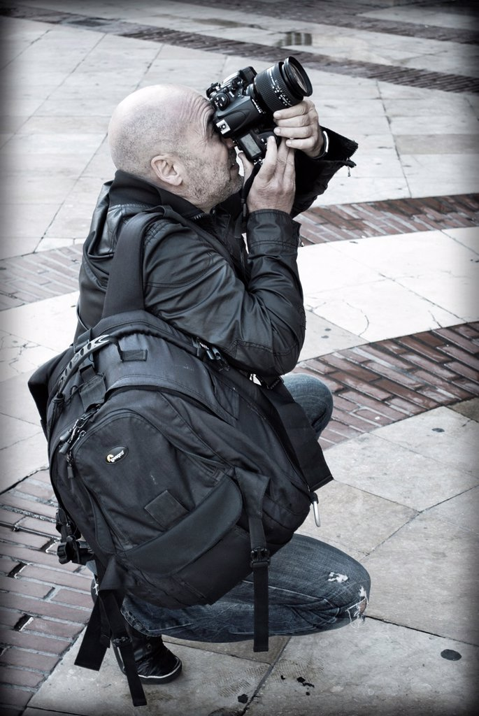 Stock Photo: 1566-1086122 Professional Photographer backpacking, crouching and concentrate, making a fotgrafía with a digital SLR camera.
