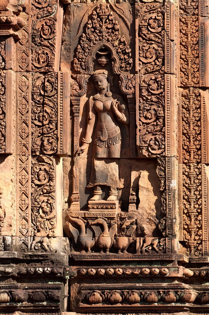 Stock Photo: 1566-1088146 Divinity as temple guardian with plaited hair wearing heavy earrings and and garlands of pearls, at the base below her feet represenatation of hamsas wild goose, niche of central tower, Banteay Srei temple, Citadel of the Women, Angkor, Cambodia
