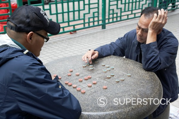 chinese men playing chinese chess at an outdoor municipal park table in hong kong hksar china asia : Stock Photo