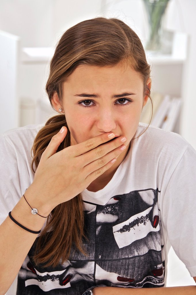 Teenage girl putting her hand in front of her mouth : afraid, forgot something, belching, stomach problems, etc.... : Stock Photo
