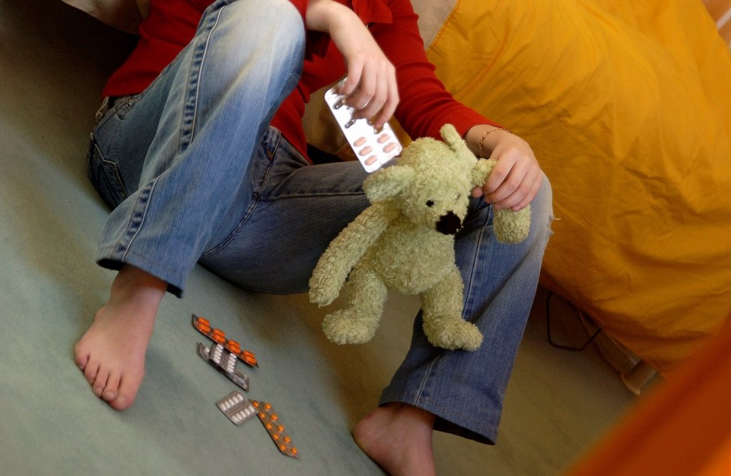 Stock Photo: 1566-1093625 Lonely teenager with soft toy and drugs