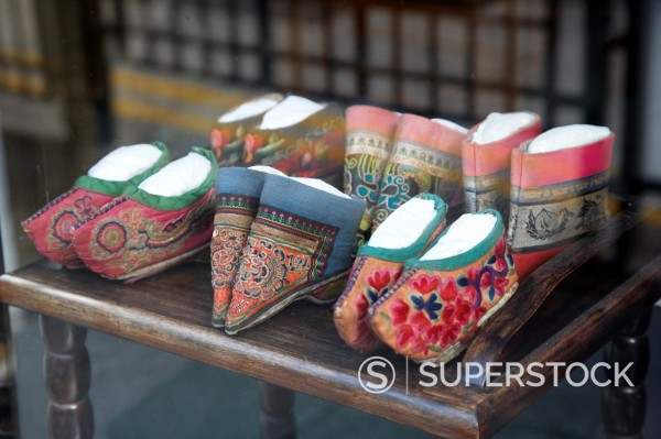 folk style traditional miniature embroidered slippers shoes in a shop window hong kong hksar china asia  the square shoes would have been used for women with bound feet : Stock Photo