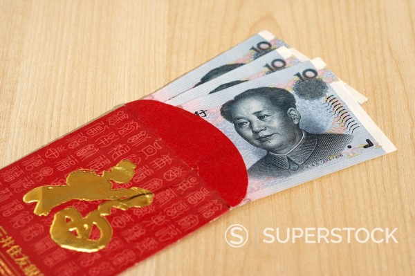 Stock Photo: 1566-1097198 chinese yuan renminbi cash currency in a red and gold gift envelope traditionally given in china at new year or for weddings