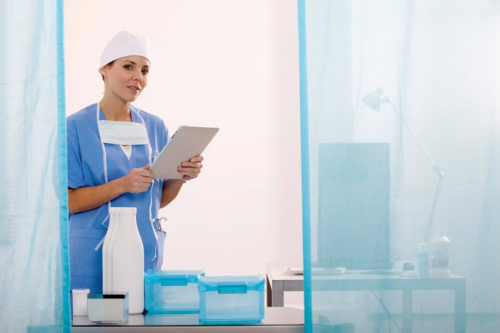 Stock Photo: 1566-1100289 Female Nurse reviewing medical records on a tablet computer