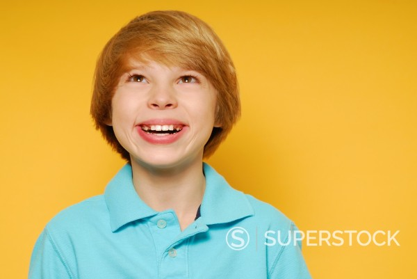 Stock Photo: 1566-1100973 Cute eleven year old boy is smiling and looking up toward the top of the frame