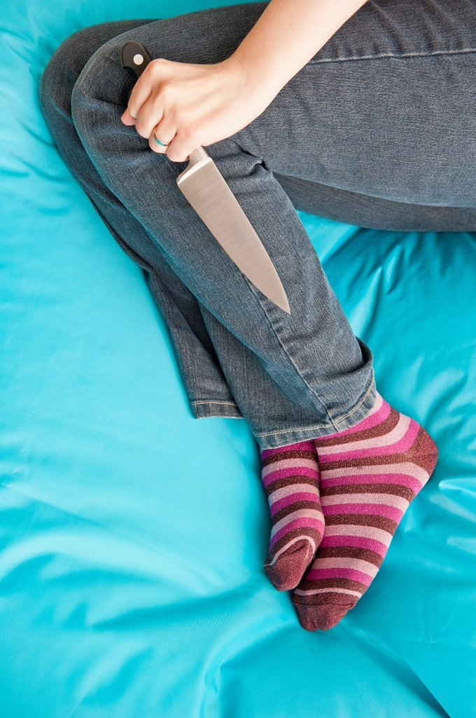 Stock Photo: 1566-1103741 Woman lying down and holding a knife in a firm grip