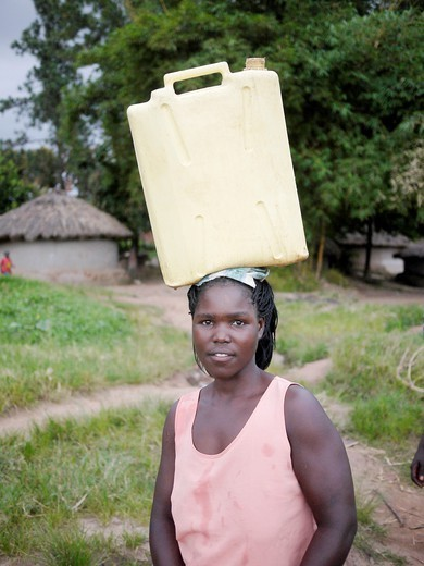 Collecting water from hand-pumped well, Gulu, Uganda : Stock Photo